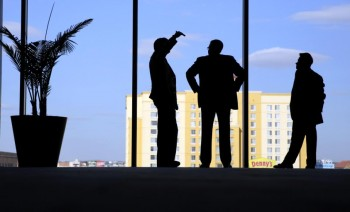 Counsel members talks as they stand at a window during a break in a closed-door meeting at  the NCAA Convention where the Big 12 is pushing to deregulate conference championship games, Wednesday, Jan. 13, 2016, in San Antonio. A move could allow the 10-team league to hold a championship game and others to consider changing theirs. (AP Photo/Eric Gay)
